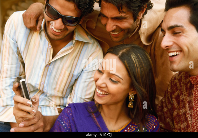Close-up of three young men and a young woman looking at a mobile phone and smiling, Agra, Uttar Pradesh, India - Stock-Bilder