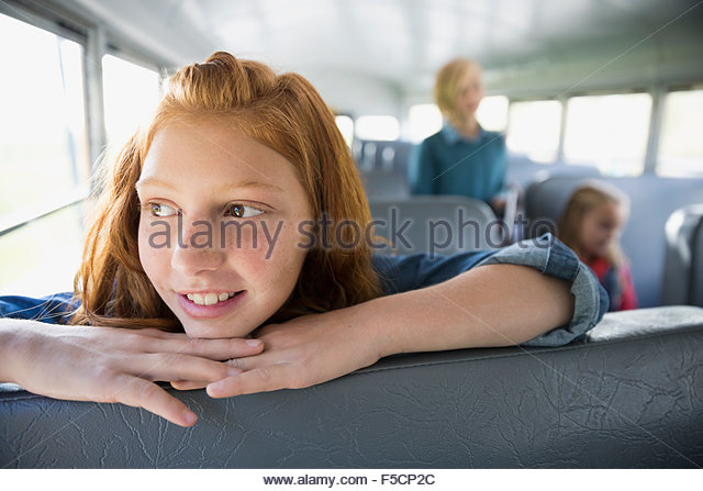 Smiling schoolgirl looking away on school bus - Stock-Bilder