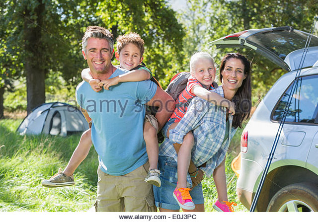 Family Flying Kite Camping Holiday In Countryside - Stock Image