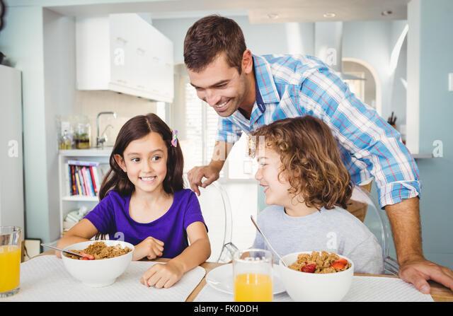 Happy man with children having breakfast - Stock Image