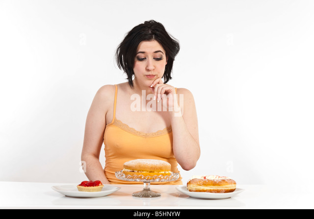 A young woman tries to decide between various cakes. - Stock Image