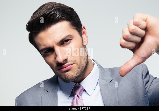 Handsome businessman showing thumb down sign over gray background. Looking at camera - Stock Image