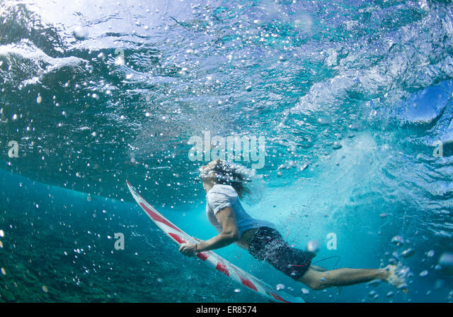 Underwater view of a surfer duck diving under a wave - Stock-Bilder