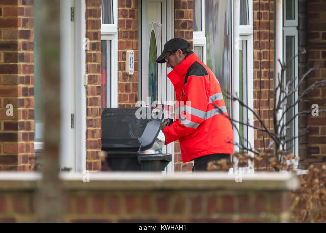 Royal Mail postman delivering post through a letter box to a house in England, UK. - Stock Image