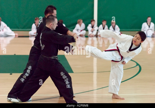A young boy breaks a wood board with a powerful kick during Tae Kwon Do black belt testing. - Stock Image