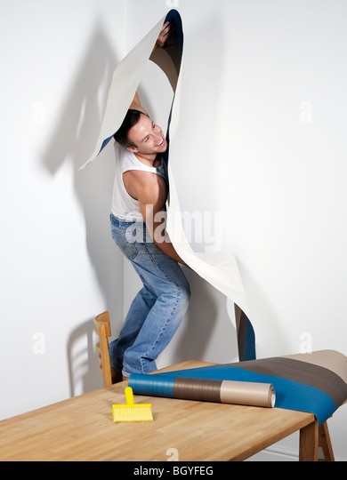 Smiling man struggling with wallpaper - Stock Image