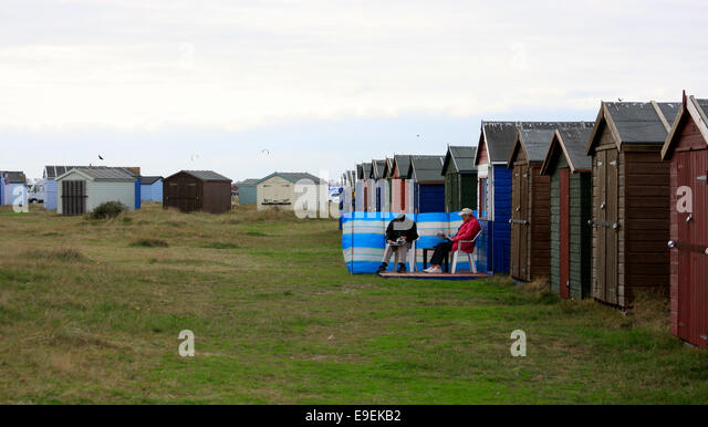 Sitting outside beach huts on Hayling Island sea front - Stock Image