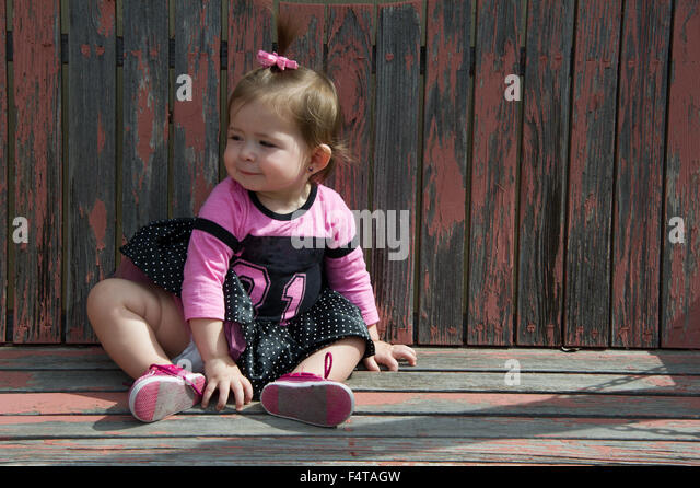 Baby girl sitting on a wood swing - Stock Image