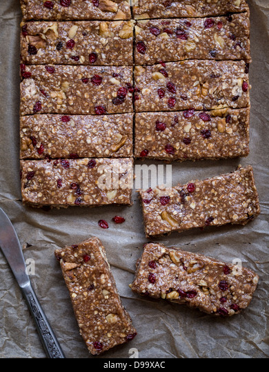Homemade chewy granola (muesli) protein bars made of peanut butter, honey, nuts and cranberries. View from above. - Stock Image