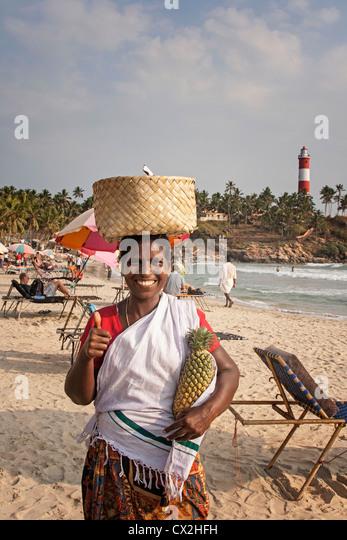 Kovallam beach, women selling pinapple, lighthouse, India Kerala - Stock Image