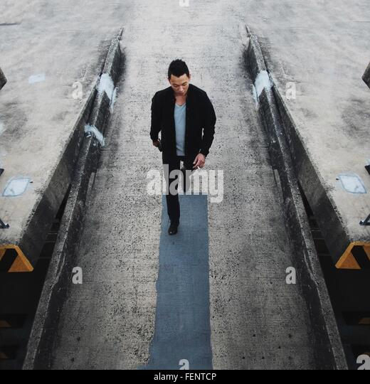 High Angle View Of Handsome Young Man Walking Down Street - Stock Image