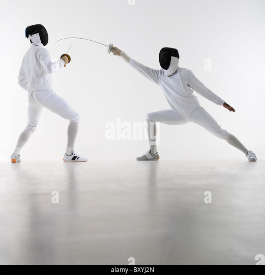 Studio shot of fencers in attacking lunge - Stock Image