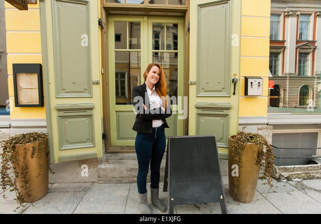 Full length of female owner standing outside restaurant - Stock Image