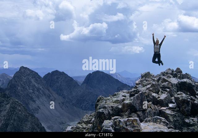 Woman jumping for joy on the summit of Vestal Peak, Weminuche Wilderness, Silverton, Colorado. - Stock Image