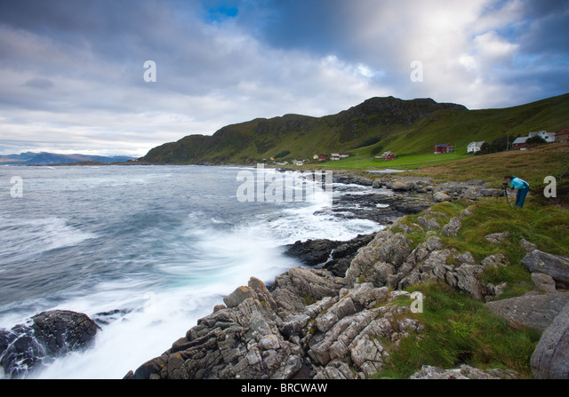 Photographer at work near the small community Goksøyr on the island Runde on the west coast of Norway. - Stock Image
