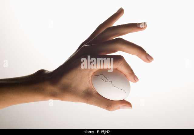 Hand holding egg with hairline crack - Stock Image
