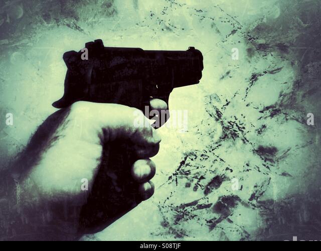 Man shooting with a gun - Stock Image