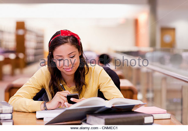 Student using cell phone and studying in library - Stock-Bilder