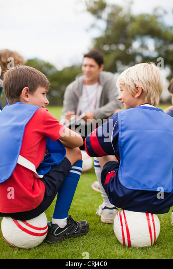 Coach talking to childrens soccer team - Stock Image