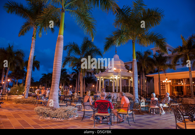 Dominican Republic, Punta Cana, Higuey, Bavaro, Riu Palace, people relaxing, piazza in the evening - Stock Image