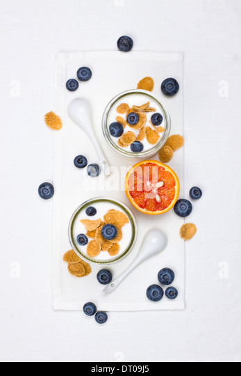 Yogurt in glasses with berries and cornflakes - Stock Image