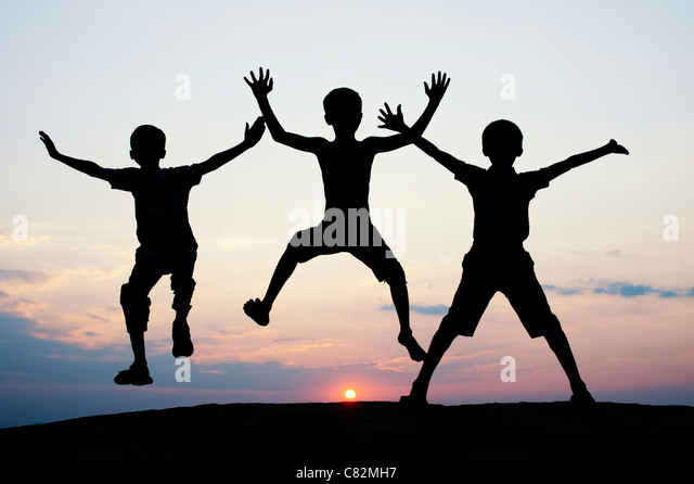 Silhouette of young Indian boys jumping against at sunset. India - Stock-Bilder