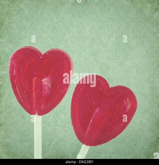 Red lollipop hearts on green vintage background - Stock-Bilder