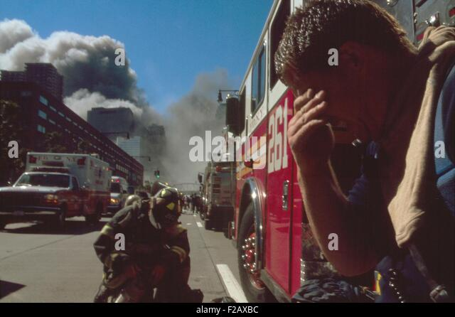 New York City fire fighter north of the collapsed Twin Towers. Behind him are other firemen, fire trucks, and rescue - Stock-Bilder