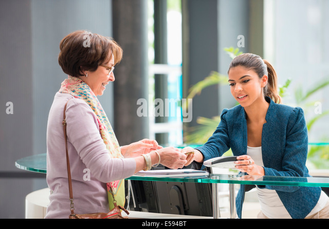 Woman making payment with credit card at reception desk - Stock-Bilder