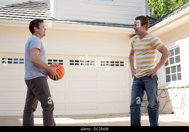 Father holding basketball with adult son - Stock Image