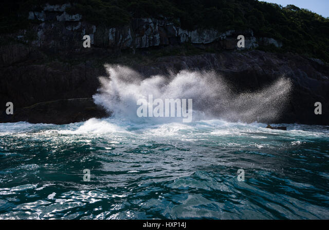 A wave crashes on the rocky cliffs of Ilhabela - Stock Image