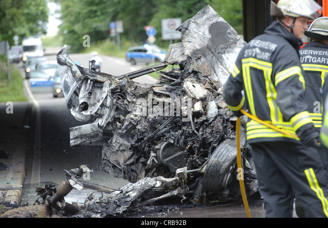 Firefighters attending the wreckage of an Audi car which was destroyed and burned out beyond recognition, Sindelfingen - Stock Image
