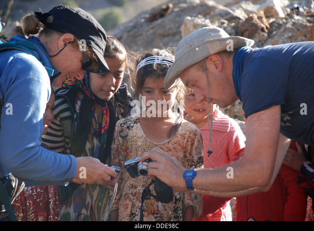 Nomad children are shown their pictures by trekkers at a camp high in the Fann mountains of tajikistan - Stock-Bilder
