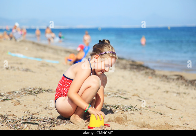 Kids playing with plastic toys on the beach - Stock Image
