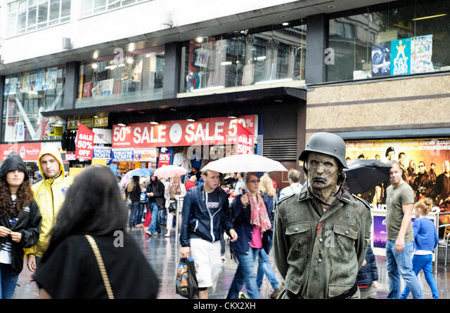Nazi Zombies stand in the rain as people walk past with umbrellas in Leicester Square. The Zombies were attending - Stock Image