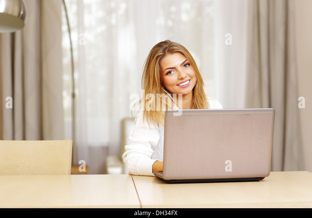 Happy young woman with laptop sitting at the table at home - Stock Image