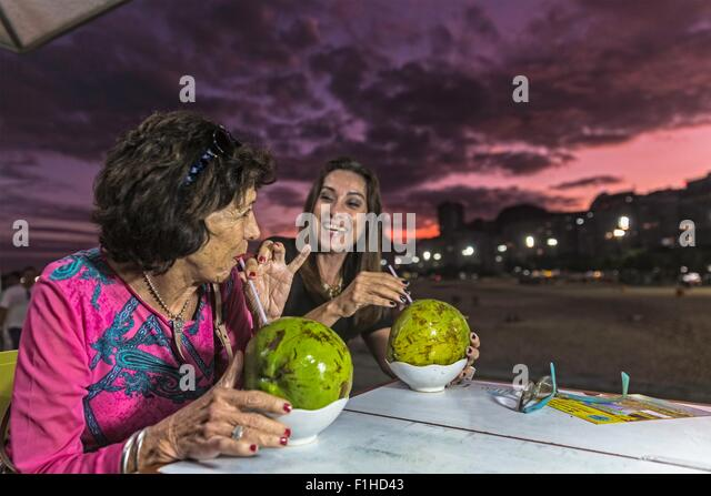 Mature woman and mother drinking from coconut shells at beach at night, Copacabana, Rio de Janeiro, Brazil - Stock Image