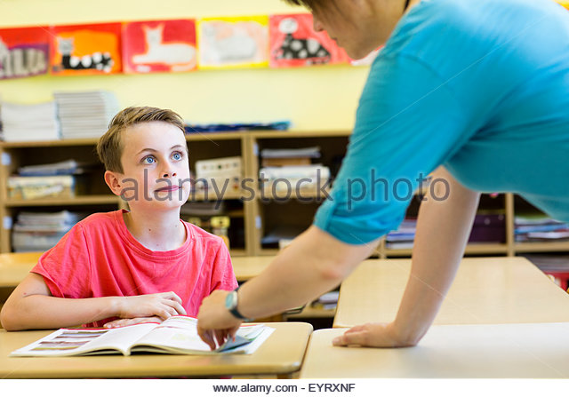 Teacher (female) and pupil (male) in the classroom - Stock Image