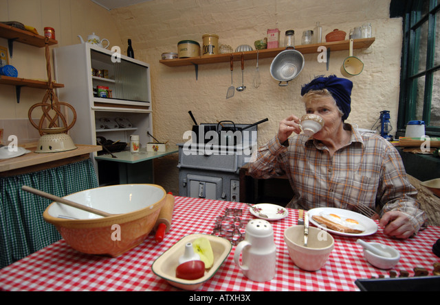 1940s kitchen with lady drinking cup of tea - Stock Image