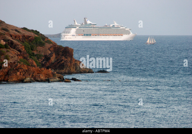 St. Thomas USVI West Gregerie Channel Water Island departing cruise ship sailboat rocky cliff Caribbean Sea - Stock Image