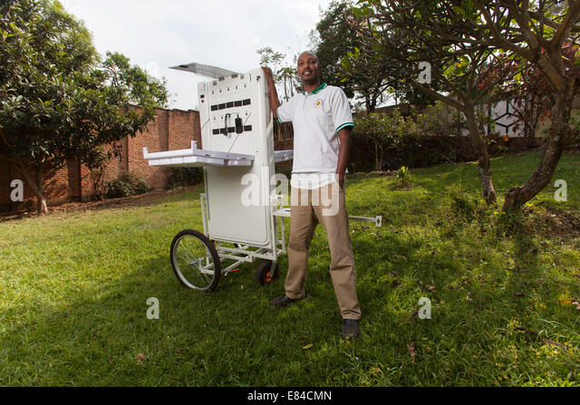 Solar energy entrepreneur posing with a portable booth designed to sell electricity in off-grid communities, Kigali, - Stock-Bilder