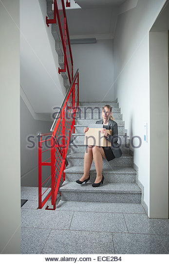 Stairs sitting sad woman jobless unemployed - Stock Image