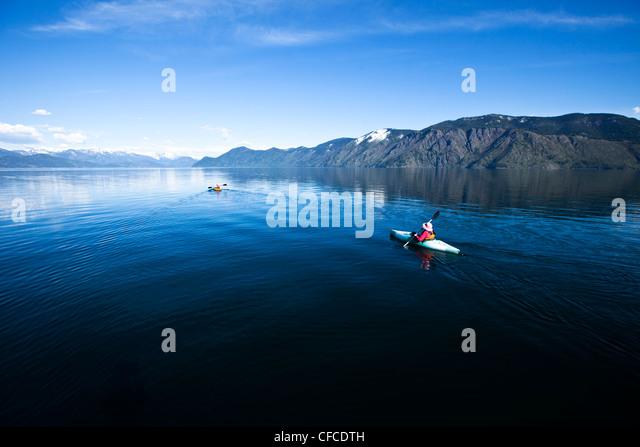An happy adventurous retired couple kayaking on a huge calm lake in Idaho. - Stock Image