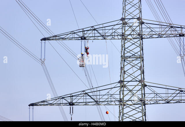 High-voltage pole, power line wire installation, man climbing to side arm, other man supporting him from a gondola, - Stock Image