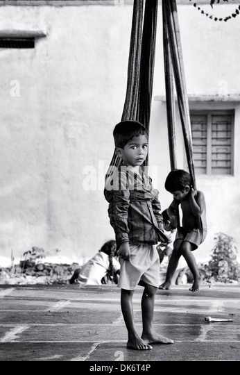 Young Indian boys playing on sari swings at home in a rural Indian village. Andhra Pradesh, India. Black and White. - Stock Image