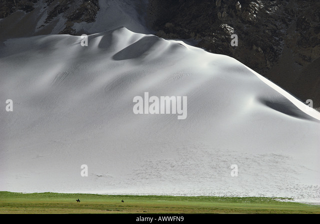 Horsemen beneath giant sand dune Pamir Range China 1980 - Stock Image