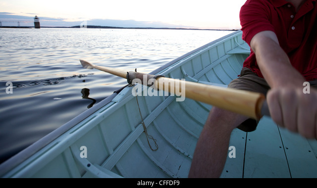 A young man rows in a Peapod dinghy at sunset along the coast of Maine near Boothbay Harbor. - Stock Image