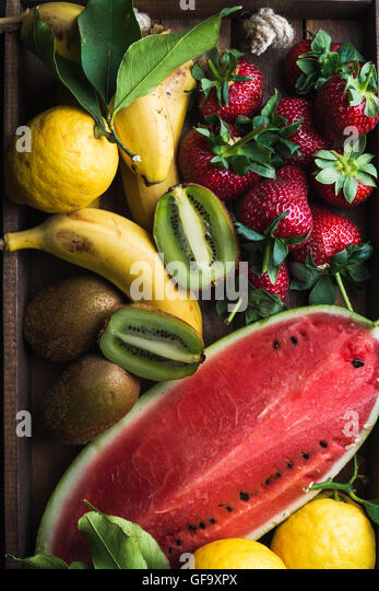 Various colorful tropical fruit selection in wooden tray over dark background - Stock Image