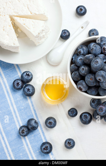 Cottage cheese, berries and honey, shot from above - Stock Image