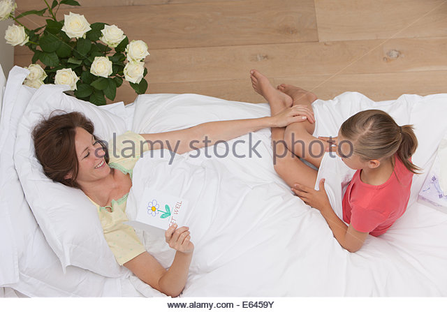 Mother laying in bed  with holding get well card - Stock Image